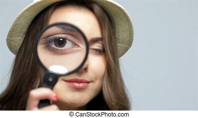 Beautiful girl with loupe zooming her eye - Girl looking...