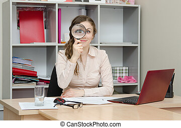 Girl looking through a magnifying glass in the office