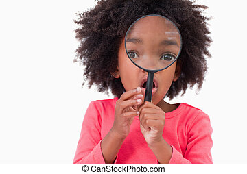 Girl looking through a magnifying glass against a white...