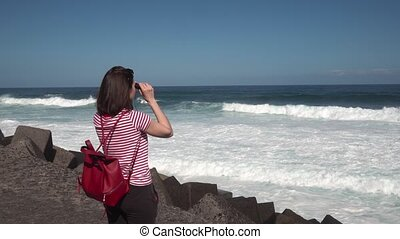 girl looking through binoculars at the ocean