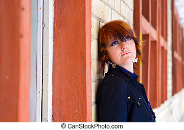 Girl Looking Up Near a Brick Wall
