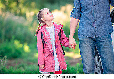 Girl looking up on father before school