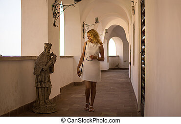 Girl looks at a sculpture in the old castle