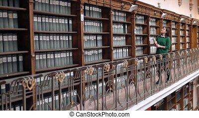 Girl Looks at Books on Shelves