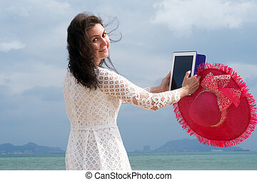 Girl looks at camera on the beach with ipad