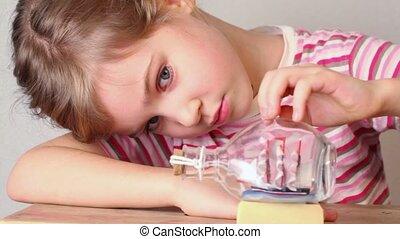 Girl looks at model of tallship in glass bottle stand on table