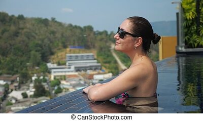 Pretty girl in black sunglasses looks at picturesque hilly landscape standing in swimming pool close up