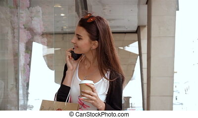girl looks at storefront holds in her hand a glass of coffee and talking on the phone