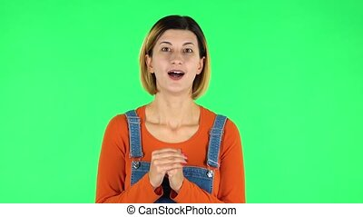Girl looks at the camera with excitement, then sighs in relief and smiles, received pleasant information. Green screen