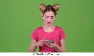 Girl looks at the phone and is surprised at what she saw. Green screen