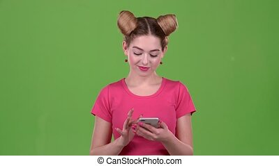 Girl looks at the phone and is surprised at what she saw, shows a thumbs up. Green screen