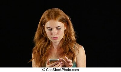 Girl looks at the photo on her phone. Black background -...