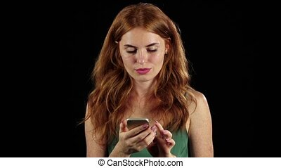 Girl looks at the photo on her phone. Black background. Slow motion