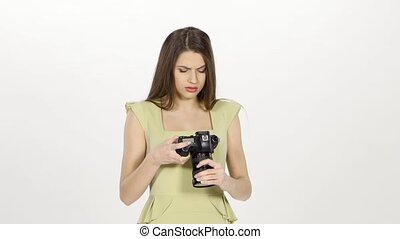 Girl looks at the results of the photo shoot on the camera screen. White