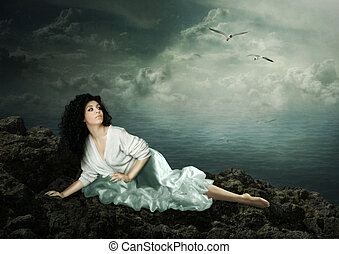 Girl looks at the seagulls - The young girl is lying on a ...