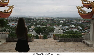 girl looks at the view of the city from the temple on the mountain Vietnam HD