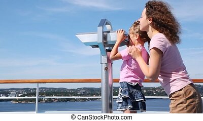 Girl looks in binocular on ship deck under direction of mother