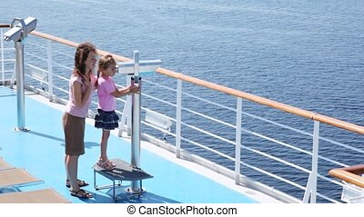 Girl looks in binocular on ship deck under direction of mother.