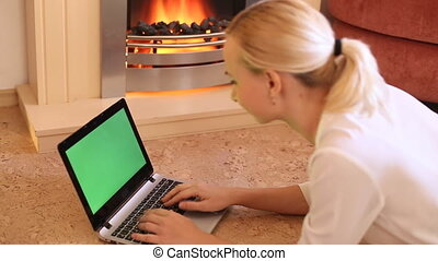 girl looks in the laptop by the fireplace