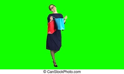 Girl looks in the shopping bags and rejoices. Green screen -...