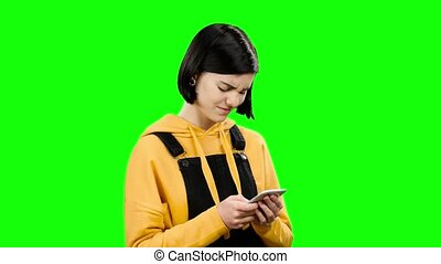 Girl looks into the phone and sees strange photos. Green...