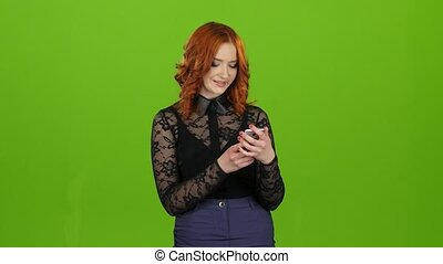 Girl looks into the phone, selects the information she...