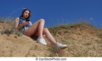 Girl looks online in a smartphone on the nature. Girl playing online games