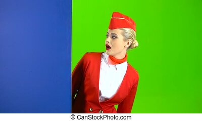 Girl looks out from behind the blue board and points at her hand . Green Screen