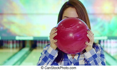 Girl looks out from behind the bowling ball