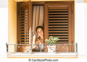 Girl looks out of the window of a country house