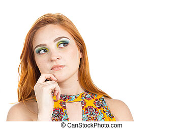 Girl looks suspiciously and looks to the side. She is in doubt. Redheaded girl wearing colorful yellow dress. Summer.