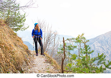 Girl looks the view during a trek in a mountain trail