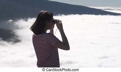 girl looks through binoculars at clouds