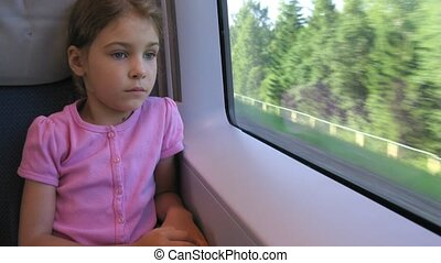 Girl looks through window in moving train, time lapse