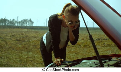 girl looks under the hood of a broken car and speaks with a...