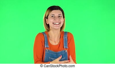 Girl looks with tenderness with folded arms in front of her. Green screen