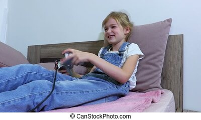Girl lying in bed and play computer game