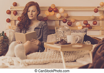 Girl lying in bed reading