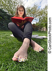 Girl Lying In Grass And Reading Book