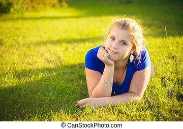 Girl lying in grass during sunny day