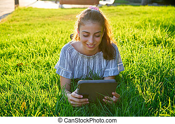 Girl lying in park  playing with tablet pc on lawn