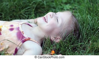 Girl lying in the grass and laughin - Child of a beautiful ...