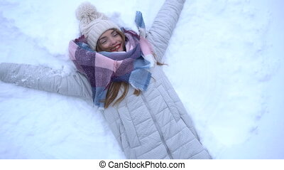 girl lying in the white snow and making an angel - Happy...