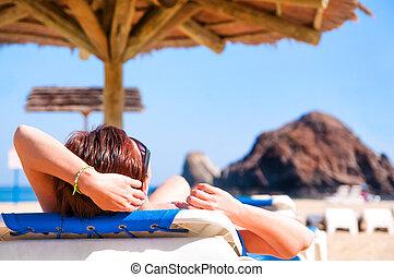 girl lying on a beach lounger