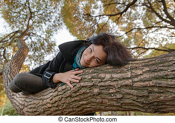 girl lying on a tree trunk