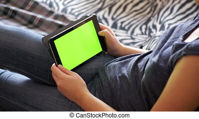 Girl Lying on Bed and using Tablet with Green Screen at...
