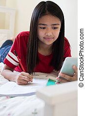 Girl Lying On Bed Using Mobile Phone To Help With Homework