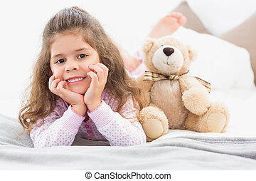 Girl lying on bed with teddy bear