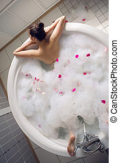 girl lying on belly in a large round white bath with foam...
