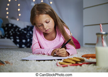 Girl lying on front and writing a letter
